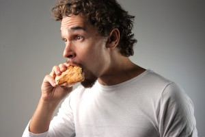 bigstock_young_man_eating_a_sandwich_12149843