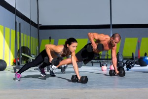 Gym man and woman push-up strength pushup with dumbbell in a wor