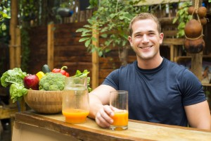 Young fitted man enjoying an organic juice and vegetable in a ra