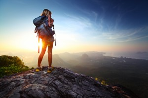 Young lady hiker standing with backpack on top of a mountain and